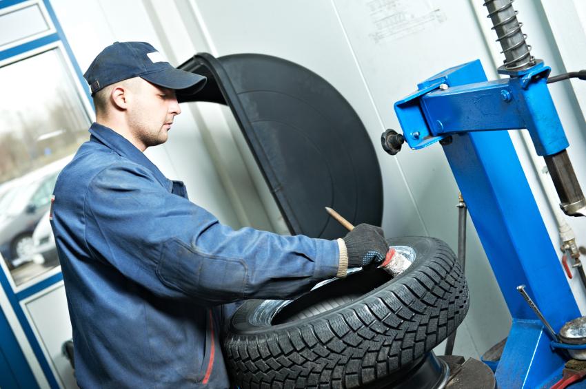 механик смазывает автомобильные шины